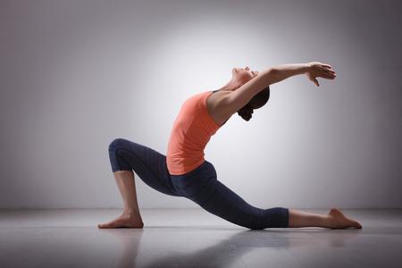 Foto de Beautiful sporty fit yogini woman practices yoga asana  Anjaneyasana - low crescent lunge pose in surya namaskar in studio - Imagen libre de derechos