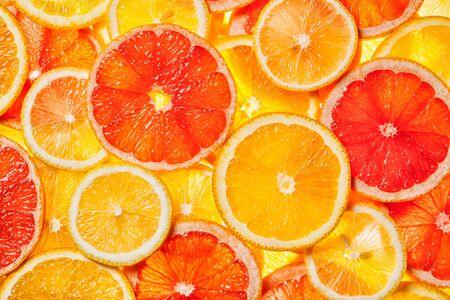 Photo pour Colorful citrus fruit - lemon, orange, grapefruit - slices background. Backlit - image libre de droit