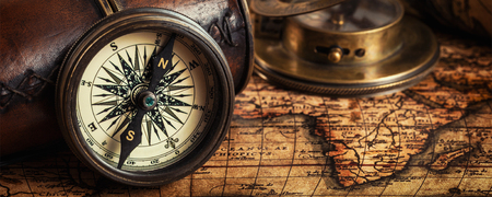 Foto de Travel geography navigation concept background - letterbox panorama of old vintage retro compass with sundial, spyglass and rope on ancient world map - Imagen libre de derechos