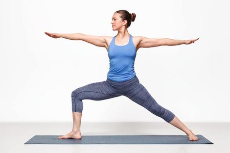 Foto de Beautiful sporty fit yogini woman practices yoga asana Virabhadrasana 2 - warrior pose 2 - Imagen libre de derechos