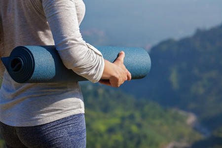 Photo for Woman standing with yoga mat outdoors in mountains close up with copyspace getting ready for yoga exercise - Royalty Free Image