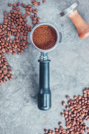 Foto de Coffee making equipment with copy space. Portafilter with ground coffee, tamper, cinnamon and beans on a marble background. - Imagen libre de derechos