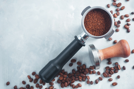 Foto de Portafilter with ground coffee close-up. Equipment for brewing coffee flat lay on a light background with copy space. - Imagen libre de derechos