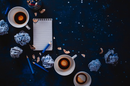 Photo for Creative writing concept with lined note paper, empty coffee cups, pencils and crumpled paper balls on a dark background. Editing and copywriting workplace. - Royalty Free Image