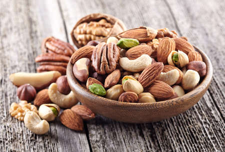 Photo for Nuts mix in a wooden plate - Royalty Free Image