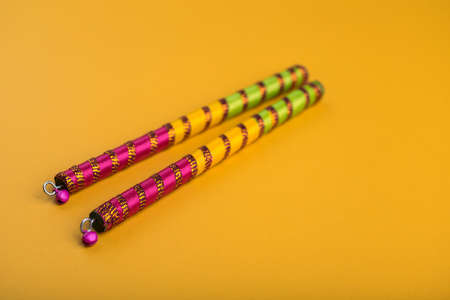 Photo pour Dandiya sticks on a yellow background. Raas Garba or Dandiya Raas is the traditional folk dance form the state of Gujarat & Rajasthan in India. - image libre de droit