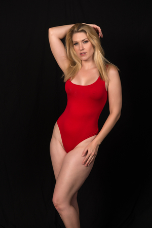 Photo for Beautiful pale blonde in a red one piece swimsuit - Royalty Free Image