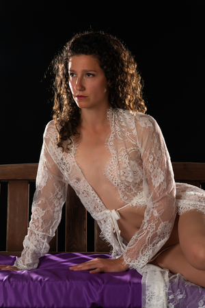 Photo pour Tall slim brunette in a sheer white lace wrap on a porch swing - image libre de droit