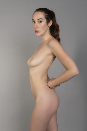 Foto de Slender tall young brunette standing nude on gray - Imagen libre de derechos