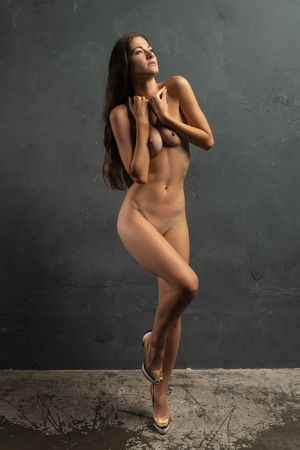 Photo for Beautiful tall brunette standing nude at a wall - Royalty Free Image
