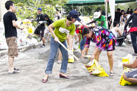 Thai volunteers fill the grit into sandbags to block the water from flood disaster in Nakornnayok province, Thailand in 15 October 2011