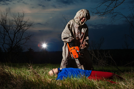 Maniac with the chainsaw dressed in a dirty bloody raincoat is killing the victim.