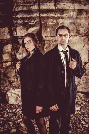 Couple of well dressed peolpe on the dark rocks background.