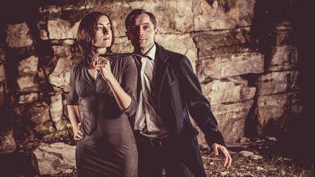 Couple of well dressed flirting peolpe on the dark rocks background.