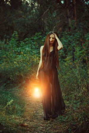Foto de Beautiful witch with the magic lantern invites you into the forest. - Imagen libre de derechos
