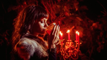Foto de Beautiful witch with the glass of vine on the night forest background. - Imagen libre de derechos
