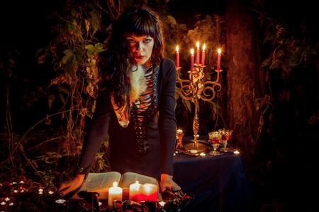 Foto de Beautiful witch with the vintage book of magic invites you into the forest. - Imagen libre de derechos