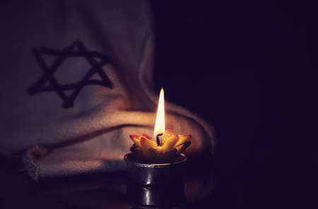 Foto de The star of David and candle stands on the table on a black background in memory of the victims of the Holocaust and genocide. - Imagen libre de derechos