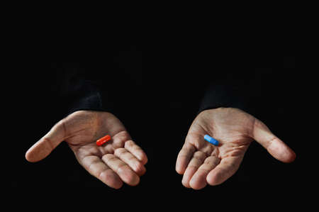 Photo pour Red and blue pills on hand isolated on black background - image libre de droit