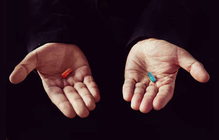 Photo pour Red tablet in the left palm blue pill in his right hand - image libre de droit