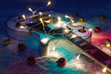 Photo for Electric guitar with lighted garland on dark background. Gift guitar classic shapes for Christmas or new year. - Royalty Free Image