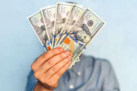Photo pour dollars in the hands. Businessman in blue shirt holding a 500 dollars. a fan of money - image libre de droit
