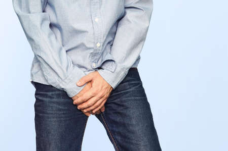 Foto de Close up of a man with hands holding his crotch on a light blue background. Urinary incontinence. Men's health. The pain from the blow in groin. - Imagen libre de derechos