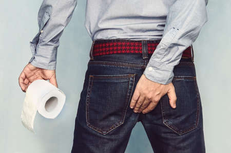 Foto de Man suffers from diarrhea holds toilet paper roll. The guy is holding the ass of himself trying to hold back the urge - Imagen libre de derechos