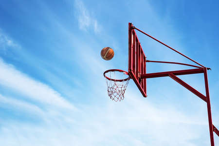Foto de Old Basketball ring on blue sky background with ball into a basket. - Imagen libre de derechos