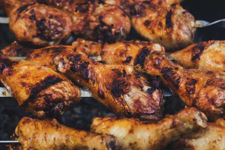 Foto de grilled chicken on a skewer with a delicious crispy fried crust. The view from the top. Hot BBQ Charcoal Flaming Grill Close-up. - Imagen libre de derechos