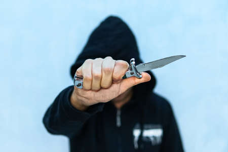 Foto de A young man in a hoodie holding a knife symbolizing youth crime. Crime concept. The threat of a cold weapon. A terrorist from ISIS with a knife. A prisoner with a Shiv. - Imagen libre de derechos