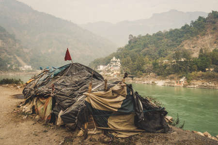 Photo for Beggar's hut by the river Ganges Rishikesh on the background of a large expensive temple. lower caste. Social inequality. The problem of poverty and the caste system of India - Royalty Free Image