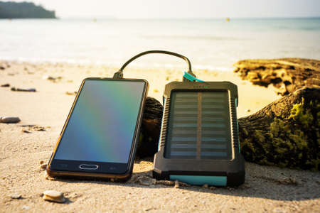 Foto de Battery solar energy device on a background of the sandy beach of an uninhabited island. Charge smart phone from the solar battery. - Imagen libre de derechos