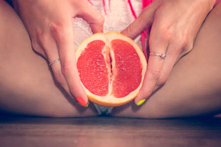 Photo for Close up of an grapefruit between woman's legs. - Royalty Free Image