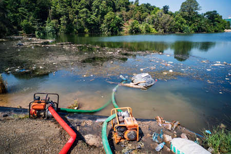 Foto de City dump in the pond in the Park. Garbage lies in the water on one of the urban landscape. plastic bottles were thrown into the water. pipes in water. - Imagen libre de derechos