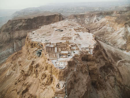 Photo pour Aerial view of Masada fortress area, ancient fortification in the Southern District of Israel situated on top of an isolated rock plateau, akin to a mesa. Ruins on the eastern edge of Judaean Desert - image libre de droit