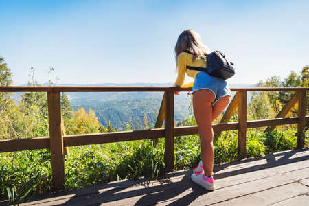 Foto de A young girl looks at the beautiful nature. The view from the back. to enjoy the scenery. Sexy woman in short shorts on a bridge in the mountains. Country walks in the countryside - Imagen libre de derechos