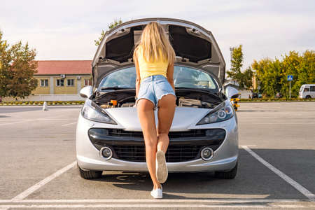 Photo for open the hood of the gray car. Photo of back of young girl in short shorts mending car on street Parking in the city in summer day - Royalty Free Image