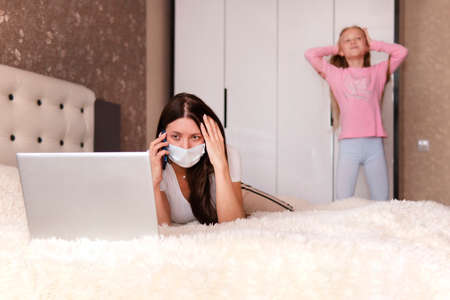 Foto de girl calls on her smartphone. Remote work. Stay at home. Tired mother holding head, trying to work at home but baby disturbing her, bedroom interior. telephone conversation. domestic life - Imagen libre de derechos