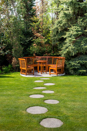 Foto de Sunny day in a spring garden with wooden table and benches - concept of lifestyle and leisure - Imagen libre de derechos