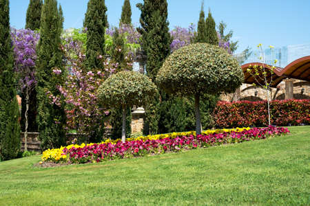 Foto de View of an attractive backyard with blooming flowers, conifers and well-kept lawns - wide angle view - Imagen libre de derechos