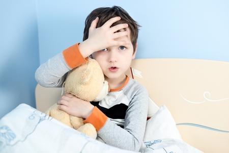 Foto de Sick little boy hugs his teddy bear in bed. Touching his forehead to check temperature - Imagen libre de derechos