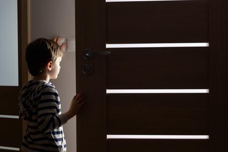 Photo pour Little boy opens the door to the room by night - image libre de droit