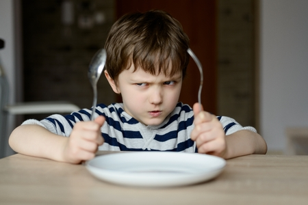 Photo pour Upset little boy waiting for dinner while holding a fork and a spoon - image libre de droit