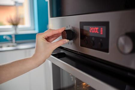 Photo pour Woman regulates the temperature of the oven - 200C - image libre de droit