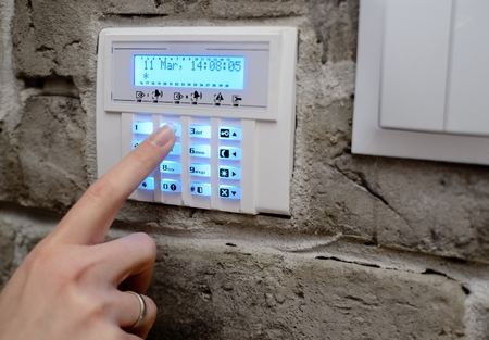 Foto de Closeup on woman's finger entering code into the keypad of the alarm system and activates the alarm - Imagen libre de derechos