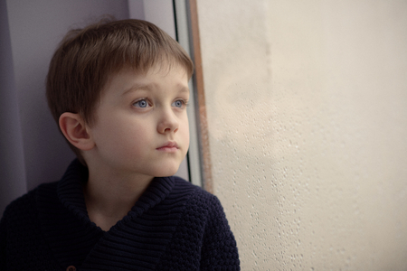 Photo pour Boy waiting by window for stop raining. Loneliness and waiting concept. Rainy day - image libre de droit