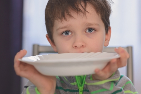 Photo pour Hungry boy with beautiful eyes waiting for dinner. Holding empty plate in his hands - image libre de droit