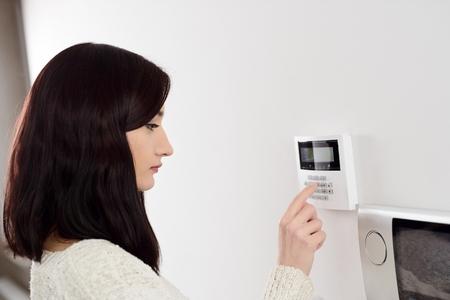 Foto de Young brunette woman entering code on keypad of home security alarm. Video intercom next to alarm keypad. - Imagen libre de derechos