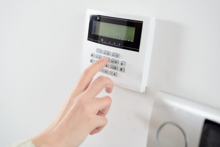 Foto de Close up on brunette woman's hand entering code on keypad of home security alarm. Video intercom next to alarm keypad. - Imagen libre de derechos